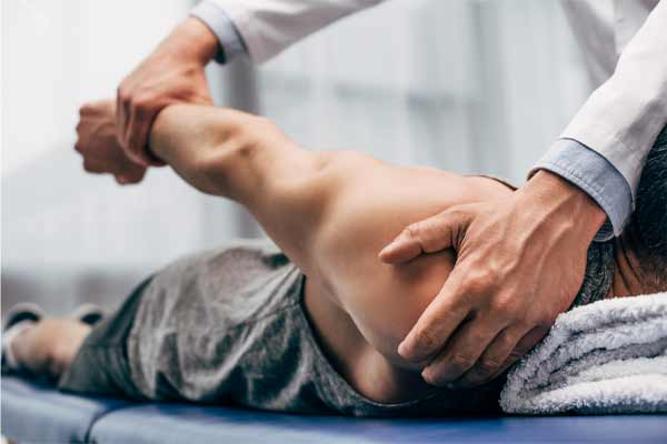 A chiropractor treating a mans shoulder injury
